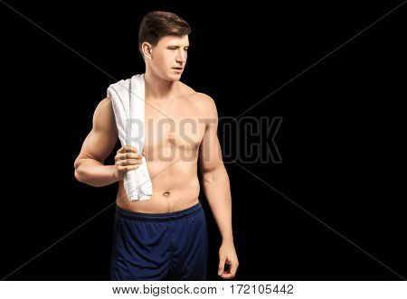 Young handsome sportsman on dark background