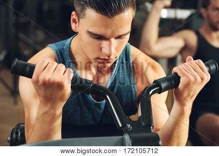 Athletic man training in modern gym