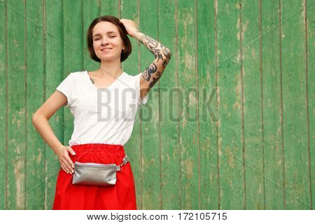 Stylish young woman with silver clutch on green wooden background