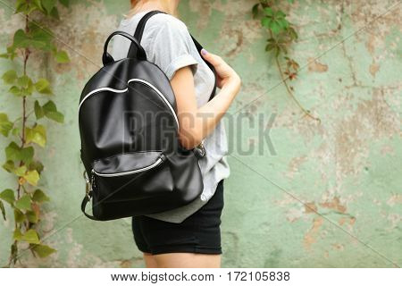 Trendy young woman with leather rucksack