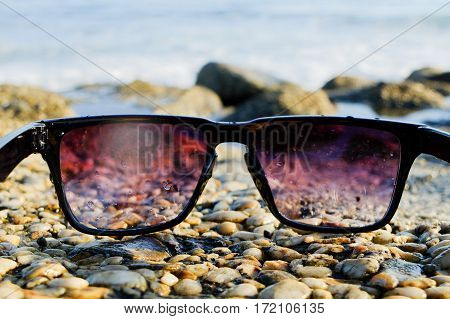 Black sunglasses lying on rocks near the sea, close up, summertime.