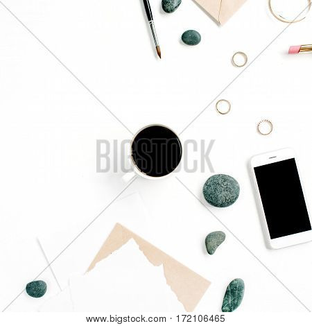 Home office workspace with coffee mobile phone craft envelope stones headphones and paper blank on white background. Flat lay top view.