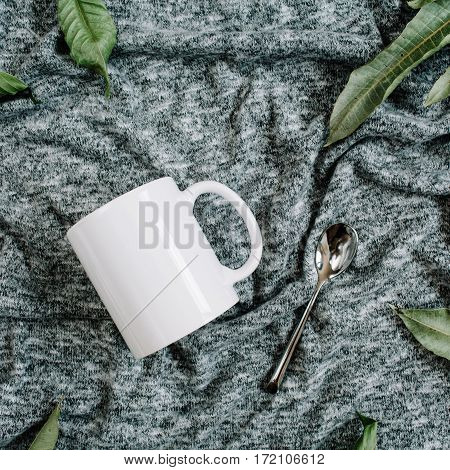 Blank template of white mug spoon and green leaves on grey textile background. Flat lay top view.