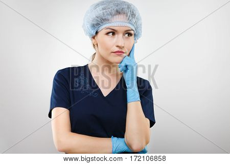 Nice nurse with nude make up wearing blue medical uniform, medical hat and gloves at gray background, copy space, posing.