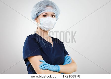 Attractive nurse with nude make up wearing blue medical uniform, medical hat and gloves at gray background, copy space.