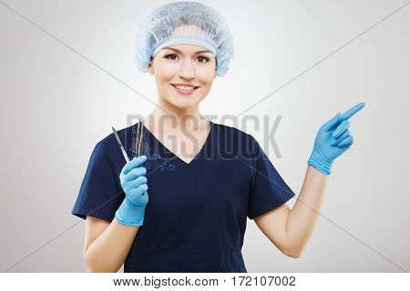 Gorgeous nurse with brown hair and nude make up wearing blue medical uniform and gloves at gray background and holding a scalpel copy space.