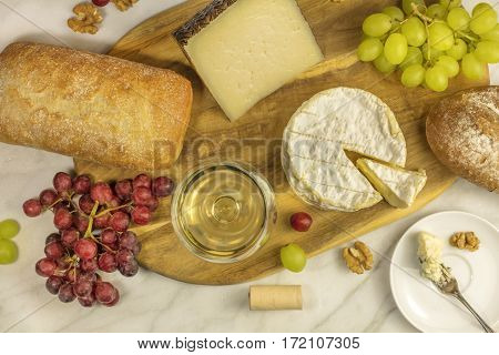 An overhead photo of a glass of white wine with cheese, white and rye bread, purple and white grapes, and walnuts, at a wine pairing