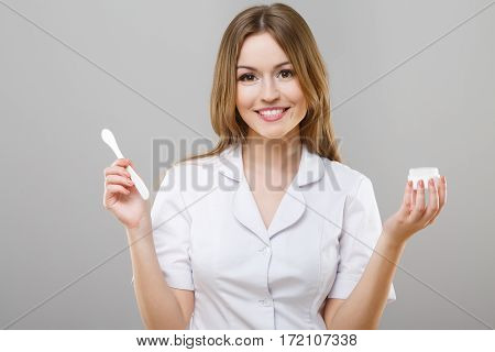 Portrait of nurse with brown hair and nude make up wearing white medical robe and holding medical product at gray background, looking at camera, portrait.