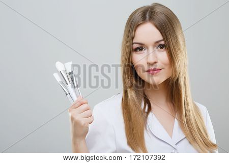 Pretty nurse with brown hair and nude make up wearing white medical robe and holding white brushes at gray background, looking at camera.