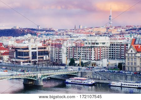 view of bridges on the Vltava river and of the historical center of Prague: buildings and landmarks of old town with red rooftops.