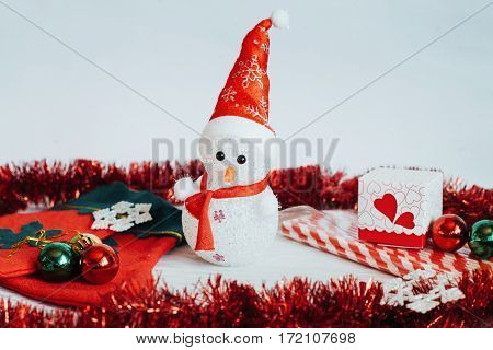 Light snowman doll and Christmas decorations on a white wooden background