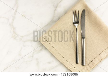 An overhead photo of a retro fork and knife on a white marble table. A restaurant menu or special offer banner design template