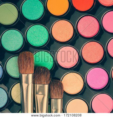 Close-up of make-up brushes on eyeshadow palette