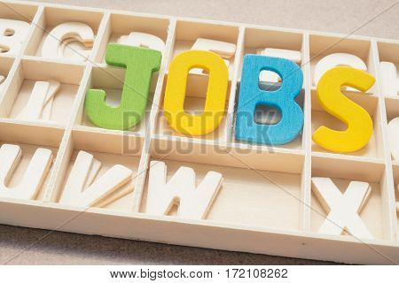 Colorful Jobs wording - text uppercase letter made from wood in the box with other letters - concept of job hunting