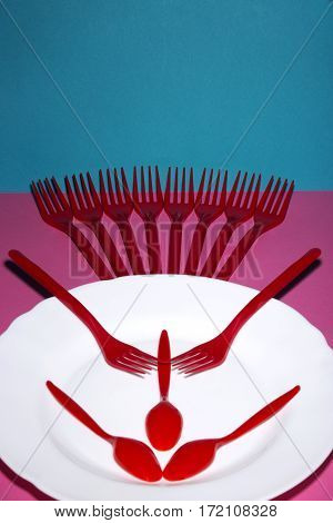 Still Life with a plastic fork and a plate on a colored background