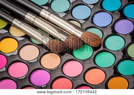 Three makeup brushes on colorful eyeshadow makeup palette