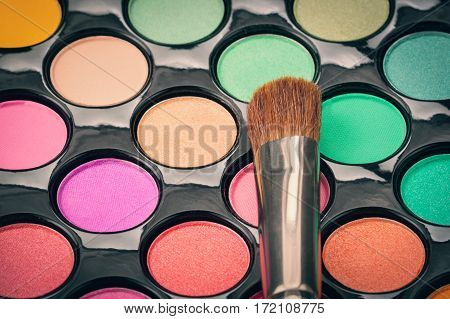 Macro shot of makeup brush with colorful eyeshadow palette