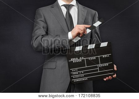 Man holding movie clapper board on black chalkboard background