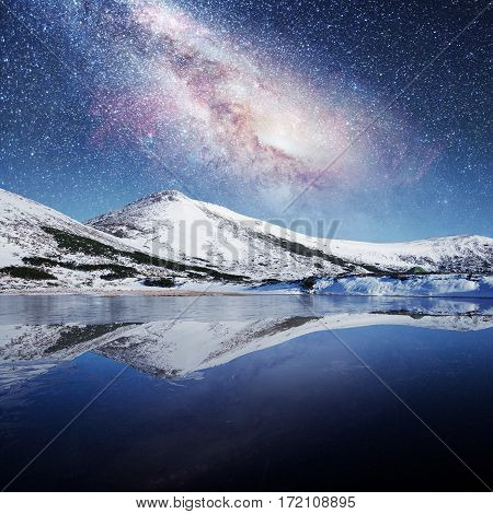 lake between snow-capped mountains. Fantastic starry sky.