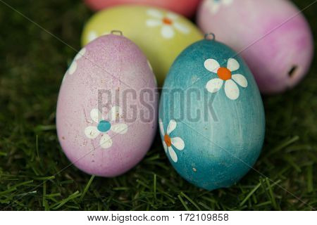 Colourful Easter Eggs with flowers painted placed on the grass