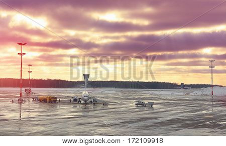 Plane on maintenance before the flight at the airport. Training aircraft for takeoff at sunset. Blue sky with clouds poured red and yellow shades. Travel Concept.