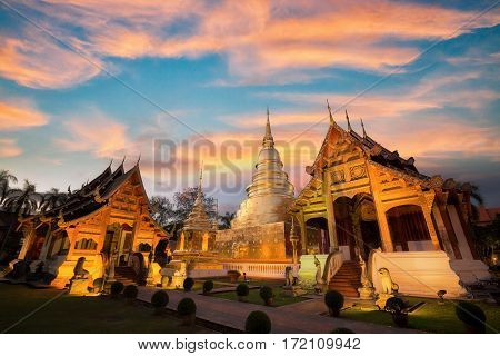 Wat Phra singh temple in chiang mai Thailand wood church and goldent pagoda with sunset sky. Phrasingh temple
