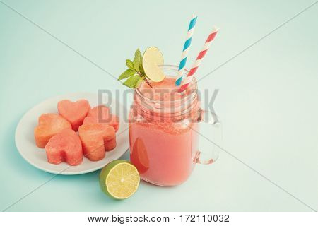 Watermelon smoothie in Mason jar decorated with lime, mint, straws with copyspace. Watermelon slices curved like hearts on plate on blue background
