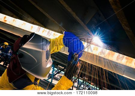 worker welding for repair bottom side of container box industrial factory and production work concept