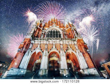 Church St. Joseph in Krakow. Fantastic starry sky. Brightly Colorful Fireworks