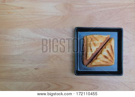 Ham cheese toast in black square disk on the plywood tabe.