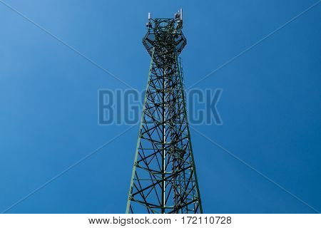 Green antenna tower with gradient blue sky background.