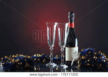 Christmas and New Year. Festive decorations, bottle of champagne and pair of flute on the dark background.