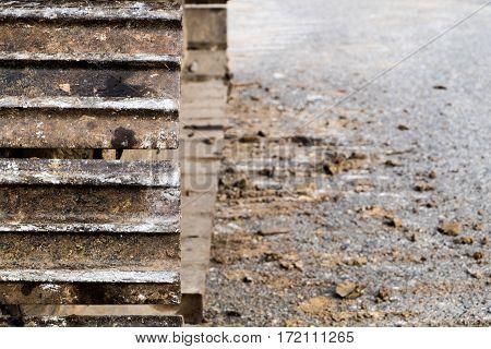 Crawler wheel part of backhoe on asphalt floor.