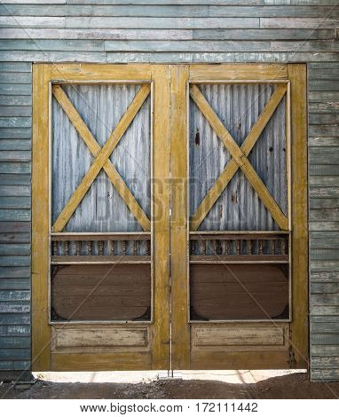 Old barn wooden bracing frame with zinc sheet double door.