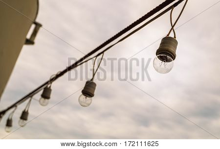 Selective focus of lamp string light hanging with rusty sling on cloudy sky background.