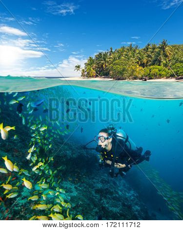 Woman scuba diver exploring sea bottom. Underwater life with beautiful corals and lots of colored fish. Half to half composition