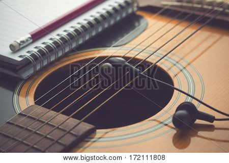 Musical Headphones and notebook on guitar. Writing music concept.