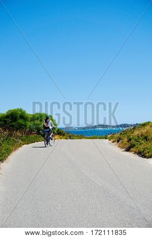 A lady cycling on an island overlooking the sea