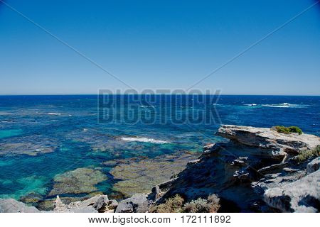 A rocky cliff overlooking the crystal blue sea