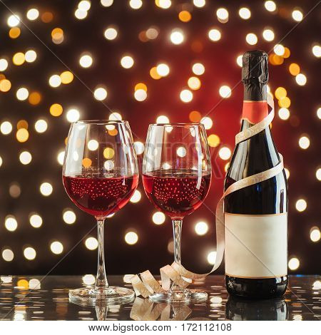 Two wine glass and red wine bottle against a dark background with gold shimmering light and bokeh