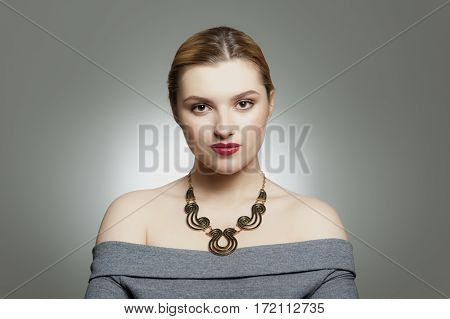 Studio portrait of a beautiful young woman with make-up and sparkle on lips