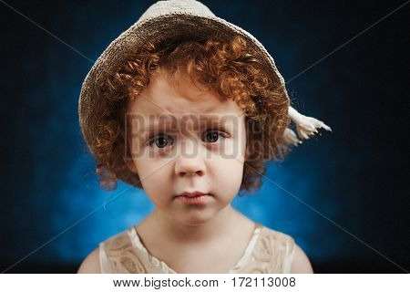 Portrait of cute little girl with hat on her head. Funny expression of shy child.