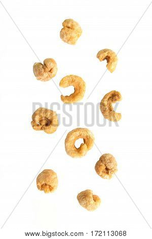 Falling pile of pork rind on white background.