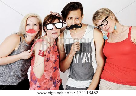 Happy hipster group having fun with artificial paper tools. Isolated on white background.
