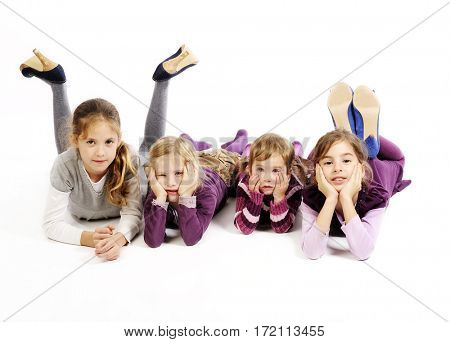 Four cute little girls are lying on the floor with legs up. Isolated on white background.