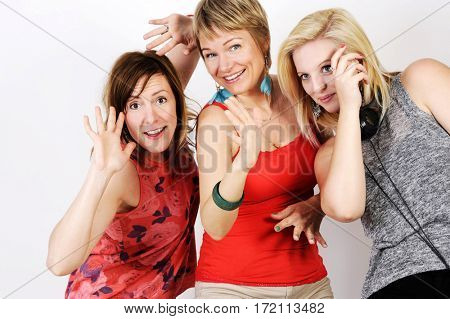 Young and trendy hipster women  having fun and dancing together. Studio shot, isolated on white background.
