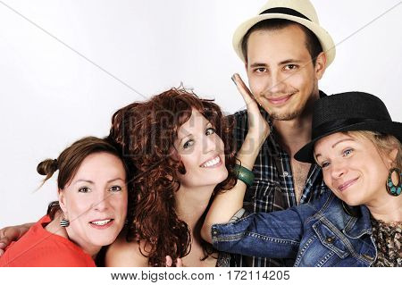 Happy smiling young group joking with hats and funny wigs. Isolated on white background.