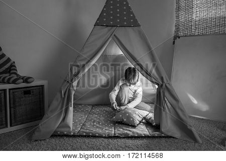 Boy playing in the teepee playroom in the lamplight.