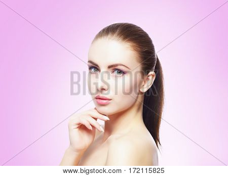 Portrait of young, beautiful and healthy woman: over violet background. Healthcare, spa, makeup and face lifting concept.