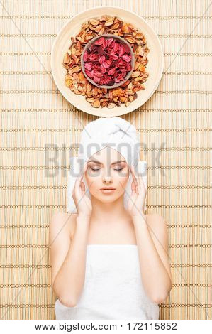 Beautiful, young and healthy woman in spa salon on bamboo mat. Spa, health and healing concept.